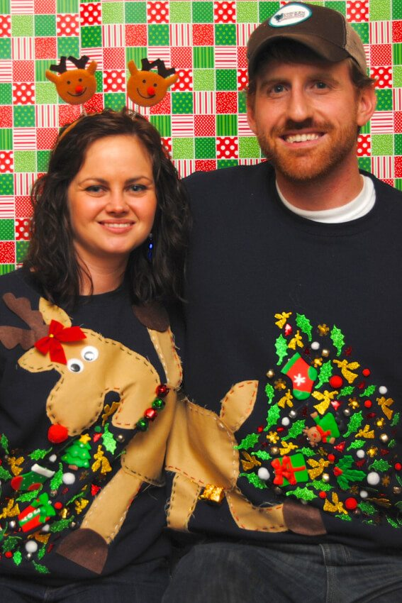 A couple putting together a picture of a puking reindeer on their ugly Christmas sweaters.