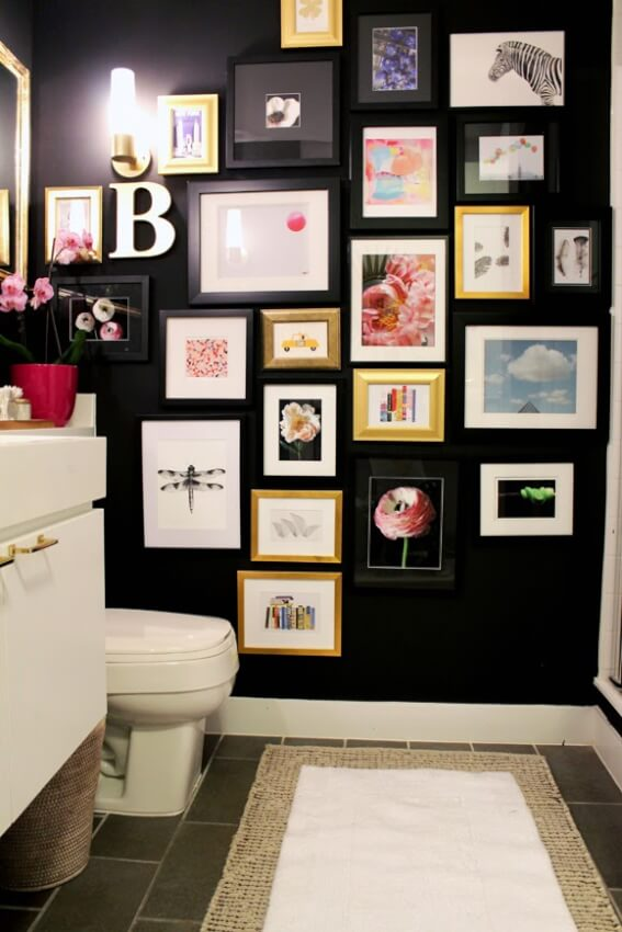 Small half bathroom painted a dark color with metal accent frames.