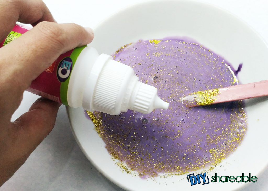 A white bowl with a purple liquid and gold glitter mixture with a wooden stirrer resting on the side of the white bowl and a hand holding a bottle about to squeeze drops into mixture