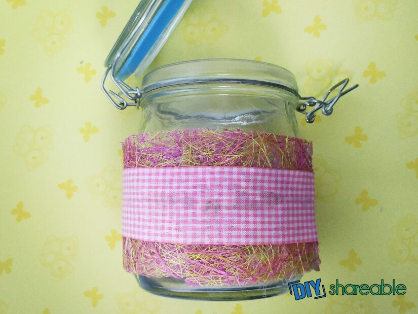 use your hot glue gun to attach the ribbon to the jar