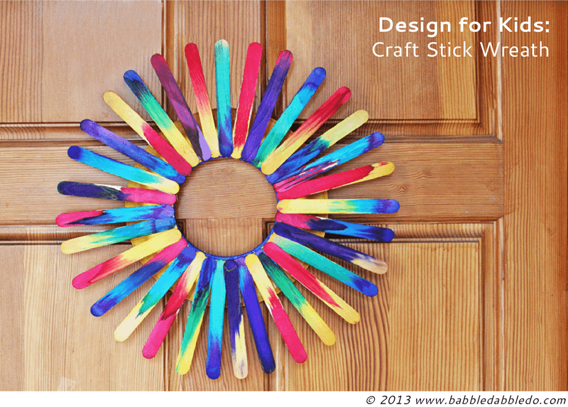 brightly colored popsicle wreath on wooden door