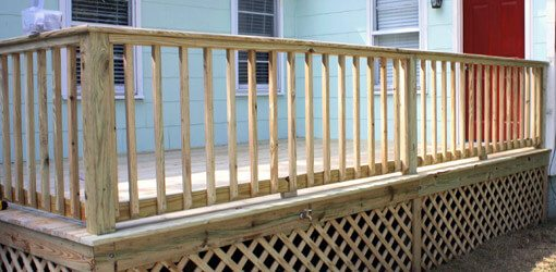 wooden deck railing with lattice work and red door