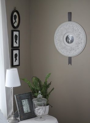 White ceiling medallion with black and white photo on beige wall next to silhouettes