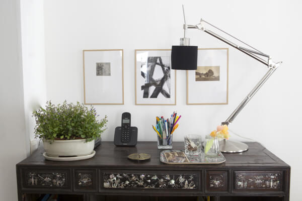 thin wood stick picture frames over desk with extendable lamp and green plant