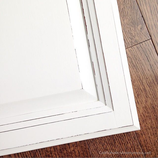 cabinet drawer painted with white chalk paint against dark wood floor