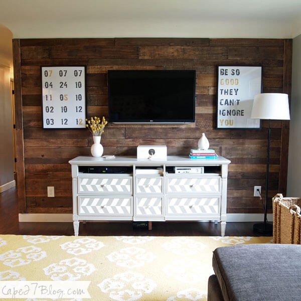 Accent wall made of wood pallets provide a cozy element to this living room.