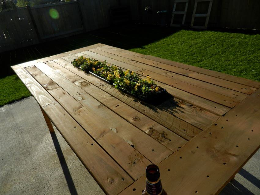 A planter table with beautiful flowers makes for a nice place to sit and enjoy your backyard.