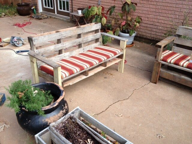 Two garden benches with cushions just completed, built with reused wooden pallets.