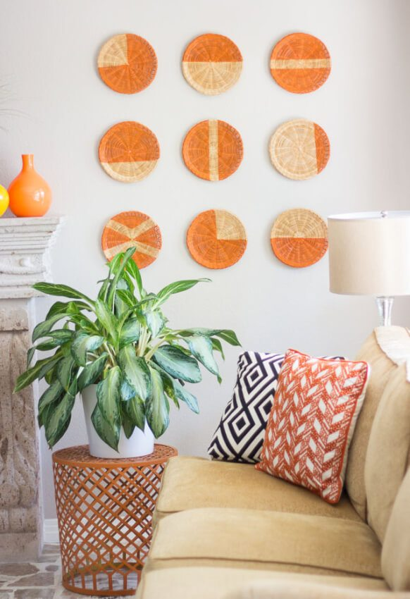 orange basket wall arrangement above tan couch with pillows and green plant