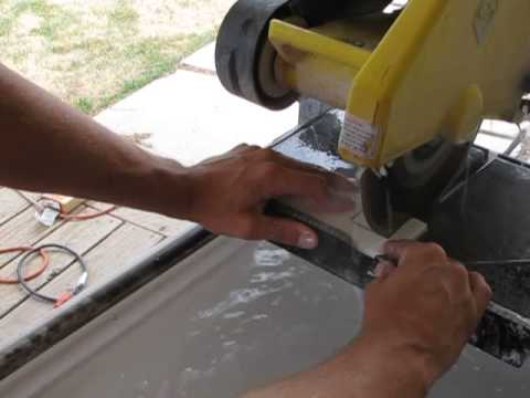 Installer cutting tile with a wet saw