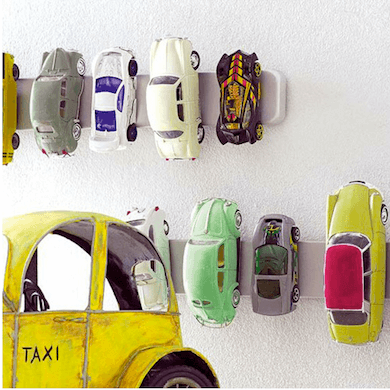 Child's matchbox cars magnetically stored on the wall using a magnetic knife strip