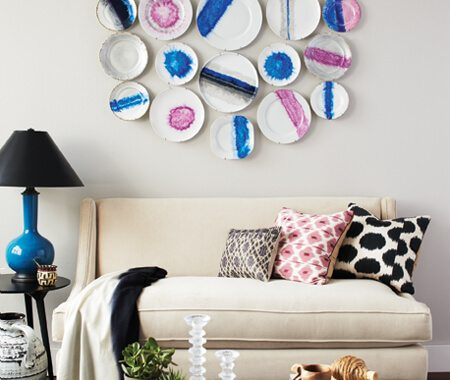 purple and blue painted plates wall arrangement above white couch with ikat pillows