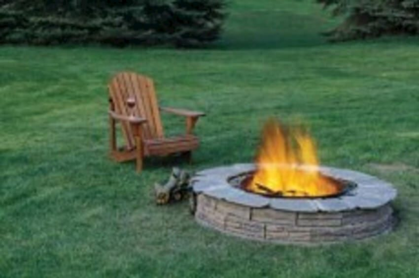 Lovely circle fire pit of classic stone in a beautiful backyard setting.