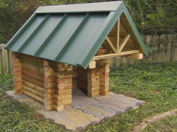 Log cabin doghouse with green roof.