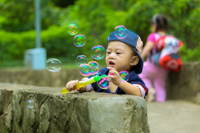 Son blowing bubbles